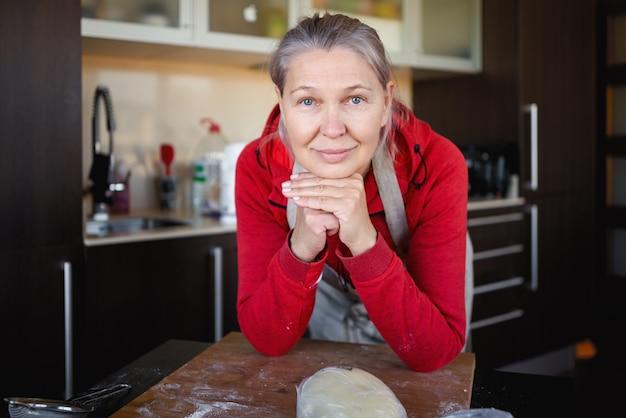 食事を準備するキッチンで成熟した女性