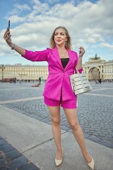 분홍색 정장을 입은 성숙한 여인이 러시아 상트 페테르부르크의 역사적인 중심지에서 스마트 폰으로 셀카를 찍고 있습니다.