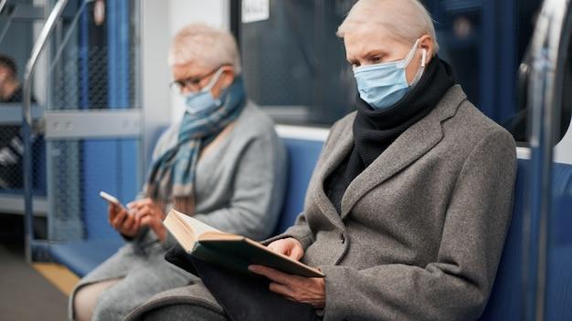 地下鉄の車に座って本を読んで保護マスクの成熟した女性