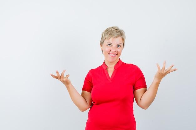 赤いtシャツを着た成熟した女性がジェスチャーを質問し、陽気に見えるように手をつないでいます。