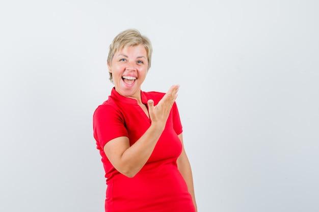 Пожилая женщина в красной футболке смеется, поднимая руку.