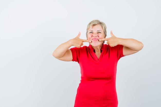 Зрелая женщина в красной футболке, указывая на ее губы и выглядя весело.