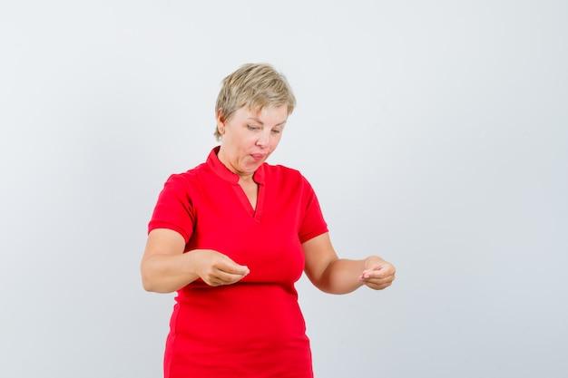 뭔가 잡고있는 척 하 고 초점을 맞춘 찾고 빨간색 티셔츠에 성숙한여 인.