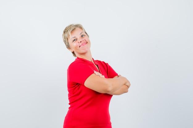 Зрелая женщина в красной футболке стоит со скрещенными руками и гордится