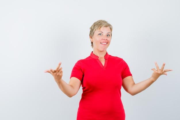 ジェスチャーに疑問を呈し、躊躇しているように見える赤いtシャツの成熟した女性