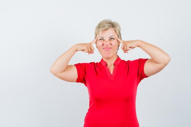 Зрелая женщина в красной футболке страдает от головной боли и выглядит неудобно