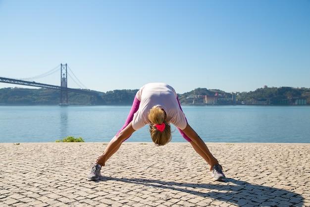 Зрелая женщина в спортивной одежде делает утреннюю зарядку на улице, растягивая мышцы спины и ног у реки. концепция деятельности или активного образа жизни