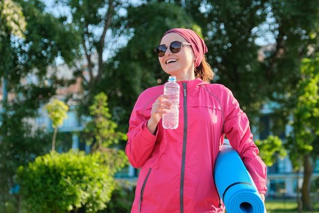 水のヨガマットボトル、屋外で歩くスポーツウインドブレーカーの成熟した女性。中年のアクティブな健康的なライフスタイル、スポーツ、フィットネス