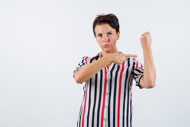 人差し指でそれを指して、自信を持って、正面図を見て、拳を握りしめている縞模様のブラウスの成熟した女性。