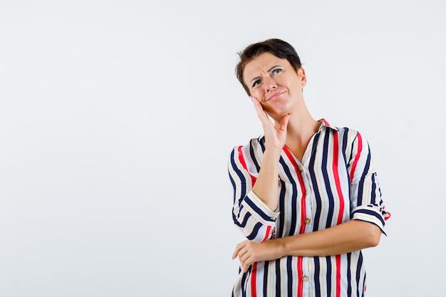 何かを考えながら、腰に手をつないで、物思いにふける、正面図を見て、手のひらに頬をもたれている縞模様のブラウスの成熟した女性。