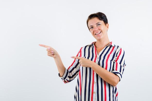人差し指で左を指し、陽気に見える縞模様のブラウスの成熟した女性、正面図。