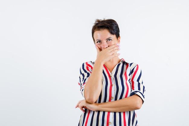 手で口を覆い、肘の下で手をつないで幸せそうに見える、正面図の縞模様のシャツの成熟した女性。