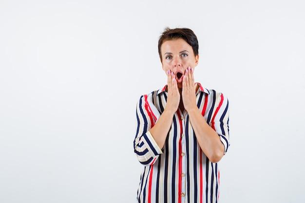 口の近くで手を握り、口を開いたまま、驚いたように見える、正面図の縞模様のシャツを着た成熟した女性。