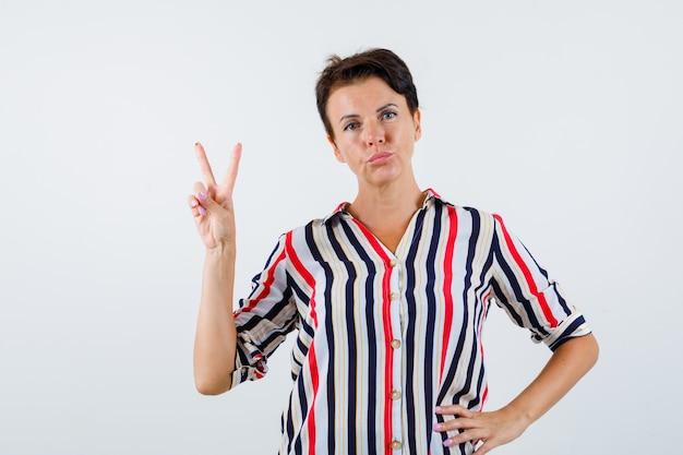 Зрелая женщина в полосатой рубашке держит одну руку на талии, показывает знак мира, изгибает губы и выглядит уверенно, вид спереди.