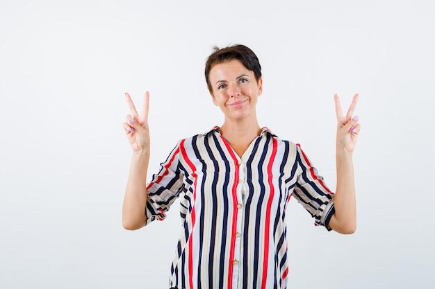 平和のジェスチャーを示し、幸せそうに見える、正面図の縞模様のシャツの成熟した女性。
