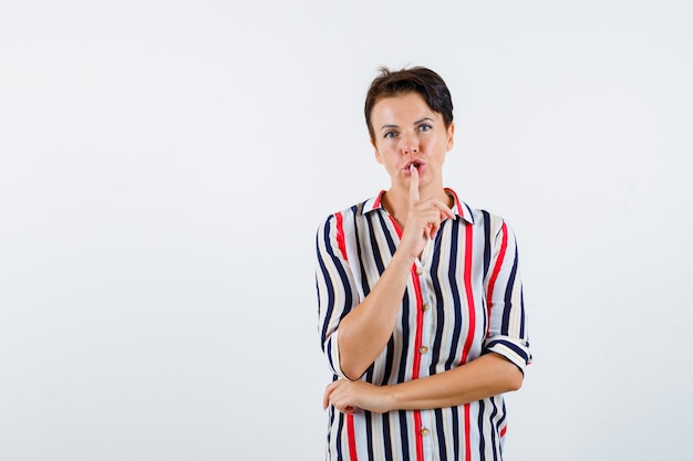 沈黙のジェスチャーを示し、真剣に見える縞模様のシャツの成熟した女性、正面図。