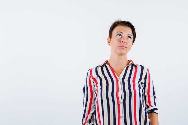 まっすぐ立って、上向きに見て、急いで、正面図の縞模様のシャツを着た成熟した女性。