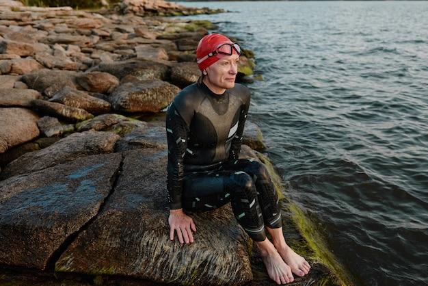 수영복을 입은 성숙한 여성이 바위에 앉아 호숫가 근처에서 수영한 후 휴식을 취하고 있습니다.