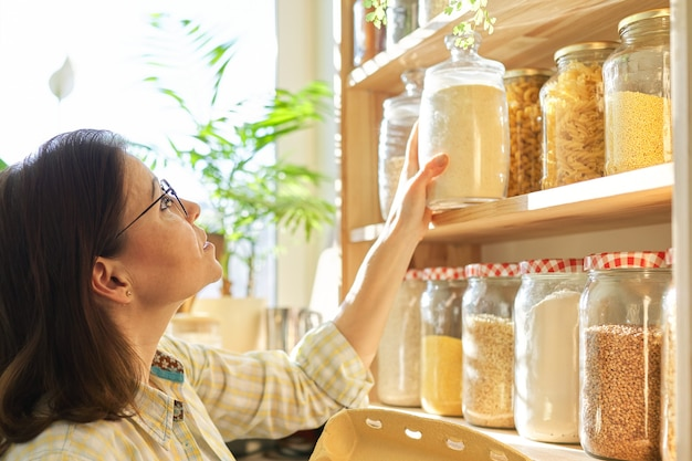Зрелая женщина в кладовой кухни с продуктами