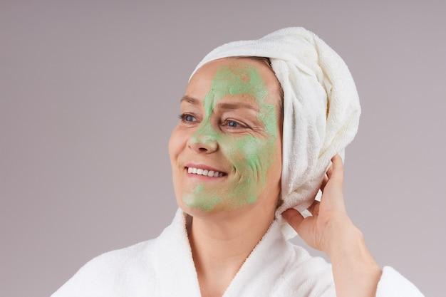 白いローブを着た成熟した女性、頭にタオル、顔に緑色のフルーツマスクを適用しました。フェイシャルスキンケアのコンセプト。灰色の壁を越えて。