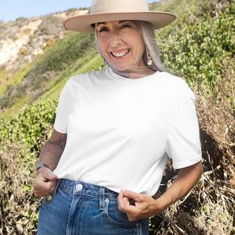 夏の屋外撮影のための白いtシャツとパナマ帽の成熟した女性