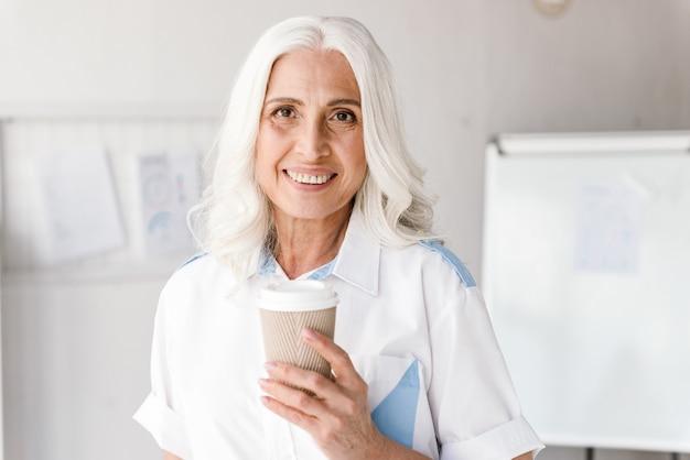 Зрелая женщина в помещении в офисе работает пить кофе