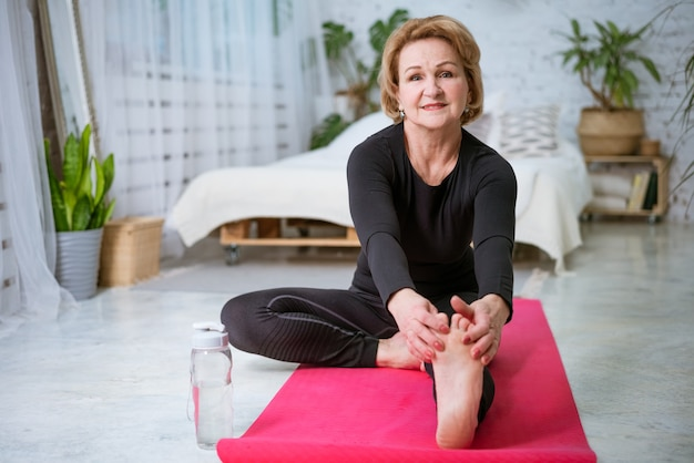 Mature woman is doing fitness on the mat at home