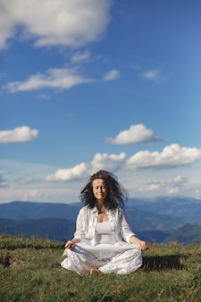 Mature woman is doing yoga. sky background of high tops of mountains.