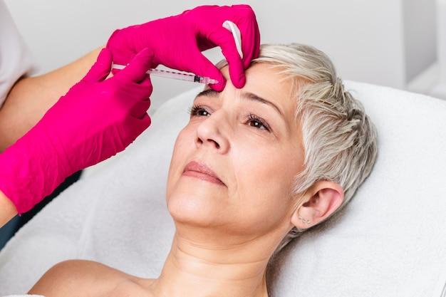 成熟した女性は若返りの顔の注射を受けています。彼女はクリニックで静かに横たわっています。専門の美容師が女性のしわにボトックスを注入しています。
