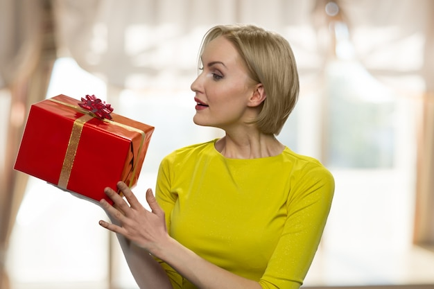 Mature woman is looking at the gift box