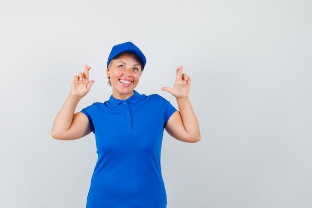 Donna matura che tiene le dita incrociate in maglietta blu e sembra gioviale