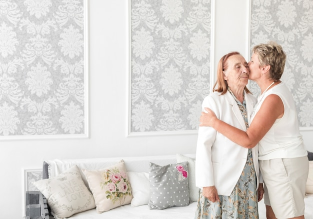 Mature woman kissing her senior mother at home