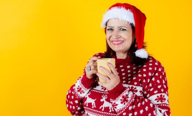 伝統的なクリスマスのマグカップで横たわっている成熟した女性。サンタクロースの帽子