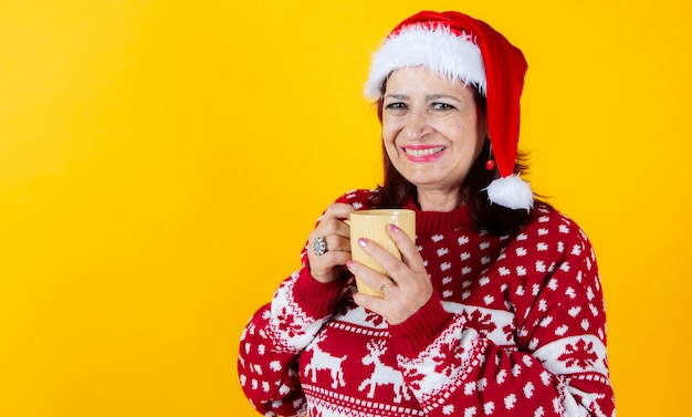 Mature woman laying with a traditional christmas mug. santa claus hat