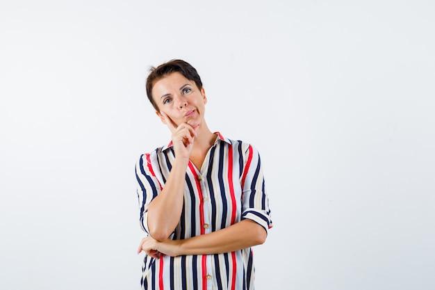 ストライプのシャツで何かを考えて物思いにふける人差し指に頬をもたれている成熟した女性。正面図。