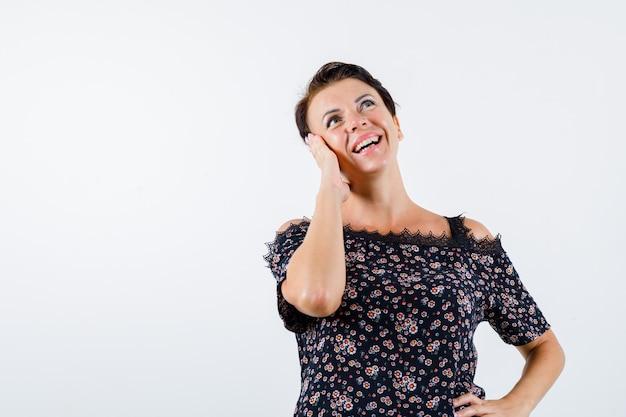 Donna matura che si appoggia la guancia sul palmo, tenendo la mano sulla vita, guardando verso l'alto in camicetta floreale, gonna nera e guardando allegro, vista frontale.