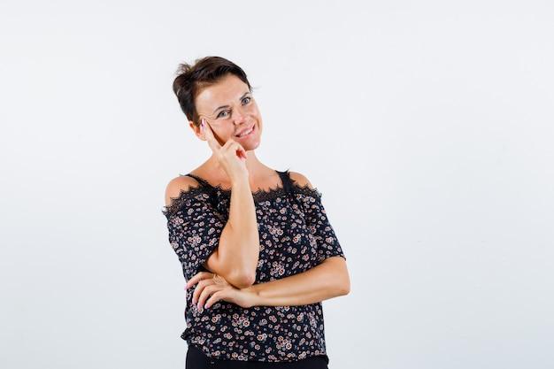 Donna matura che si appoggia la guancia sul palmo, pensando a qualcosa in camicetta floreale, gonna nera e guardando felice. vista frontale.