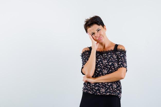 Donna matura che si appoggia la guancia sul palmo, pensando a qualcosa in camicetta floreale e gonna nera e guardando pensieroso, vista frontale.