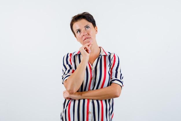 Donna matura che si appoggia il mento sul dito indice, pensando a qualcosa, mordendosi le labbra in camicetta a righe e guardando pensieroso, vista frontale.