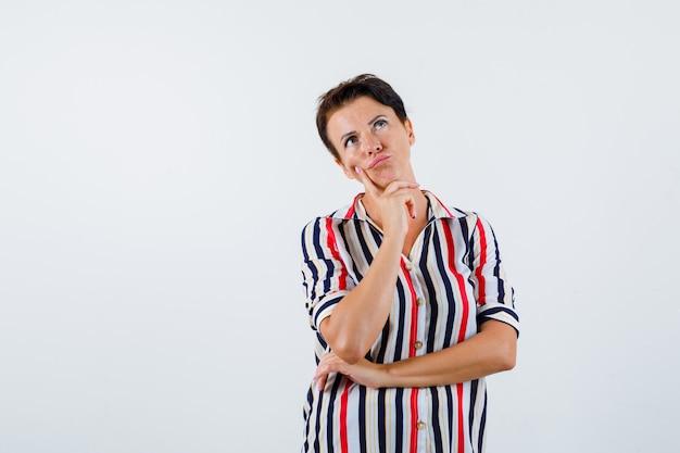 Donna matura che si appoggia il mento sul dito indice, pensando a qualcosa in camicetta a righe e guardando pensieroso, vista frontale.