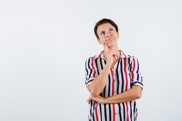 人差し指に顎をもたれ、縞模様のブラウスで何かを考え、物思いにふける、正面図の成熟した女性。