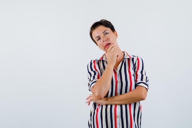 Donna matura che si appoggia il mento sul palmo, pensando a qualcosa in camicetta a righe e guardando pensieroso, vista frontale.