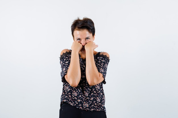 Зрелая женщина, опираясь кулаками на щеки в блузке и выглядя мило, вид спереди.