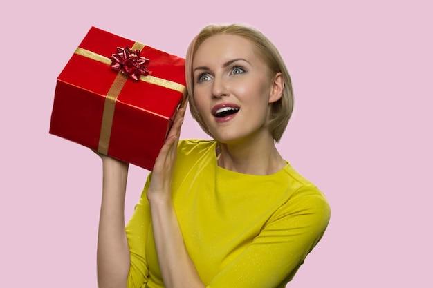 Mature woman listening to gift box