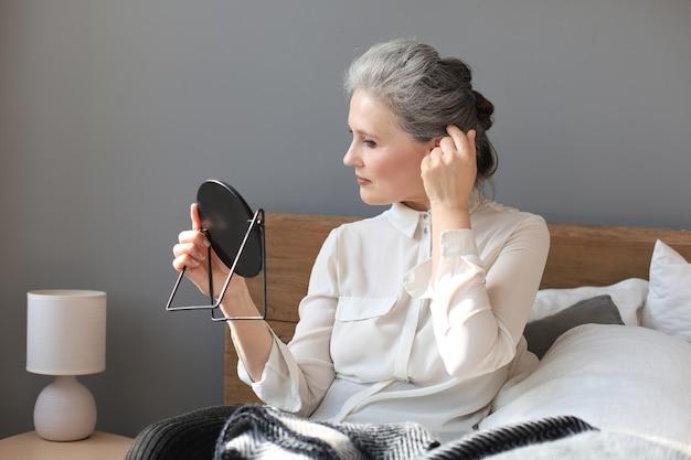 鏡を見て、自宅で顔に触れる成熟した女性。