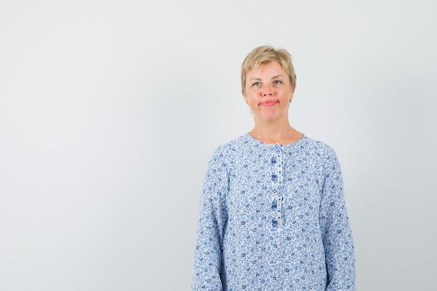 Зрелая женщина смотрит в сторону, думая в платье и недовольна