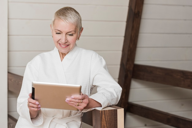 Mature woman looking on her tablet at home