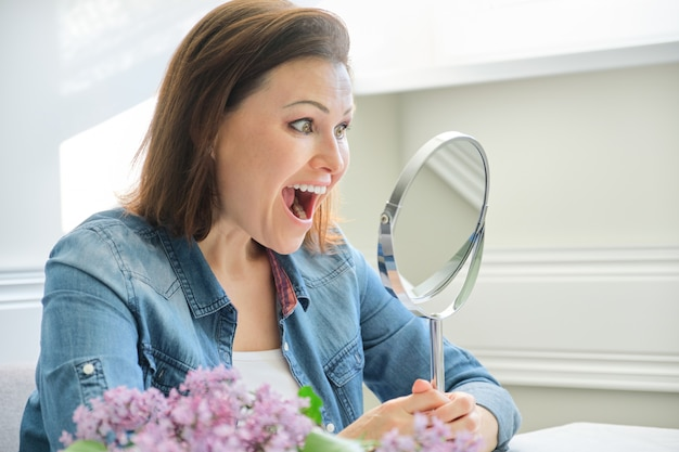 Mature woman looking in the mirror and screaming