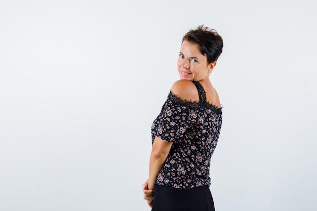 Donna matura che osserva sopra la spalla in camicetta floreale e gonna nera e sembra affascinante, vista frontale.