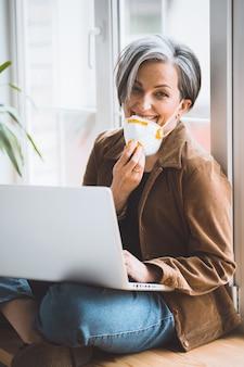 Зрелая женщина опускает маску fp1 и улыбается, глядя в камеру, пока работает портативный компьютер, сидя на